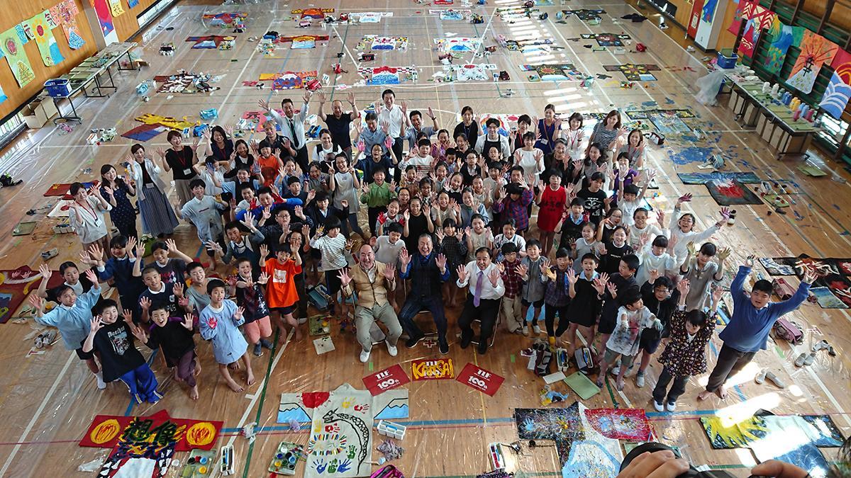 台東区立富士小学校でレザーはんてんにペイントを指導した山本寛斎さんと児童