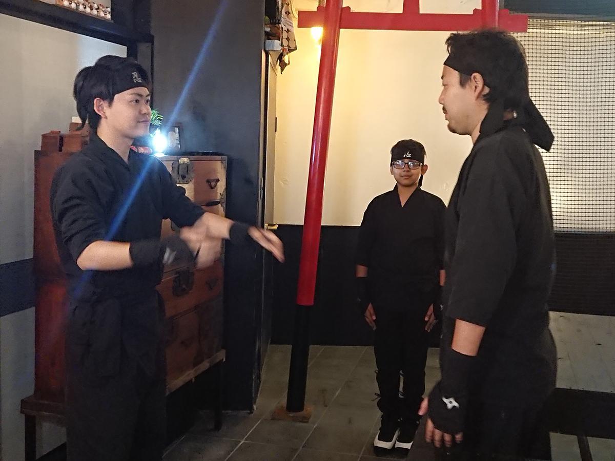 ニューヨークから訪れた男の子を前にデモンストレーションする社長の矢野智之さん(右)と、スタッフの忍者マスター秋山智惟さん(左)