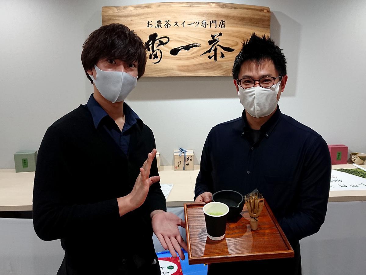 金粉入りの抹茶を手にする統括店長の剱谷哲也さん(右)とスタッフの谷島光城さん(左)