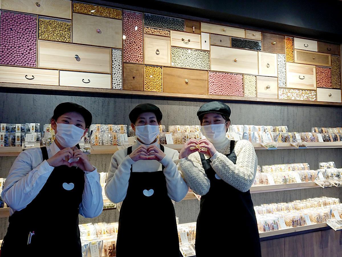 スタッフみんなで詰めたという店内ディスプレーの前で「豆ポーズ」をする青木幹子さん(右)、渡部夏花さん(真ん中)、関口美優香さん(左)
