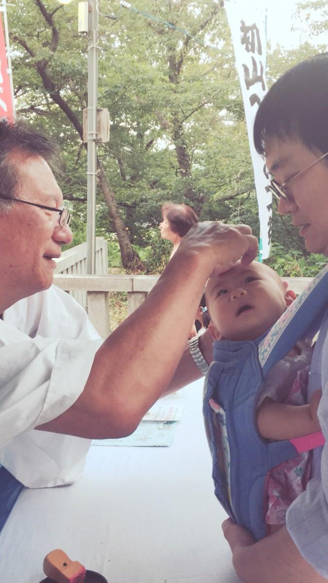 一歳になる前の赤ちゃん、お父さんに抱かれながら参拝