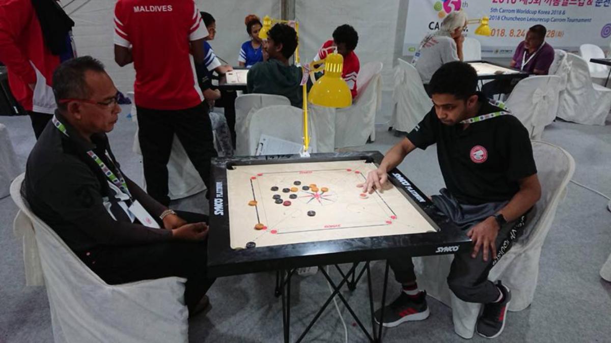 南アジアのボードゲーム「キャロム」をするダンミカ サマラセカラさん(右)