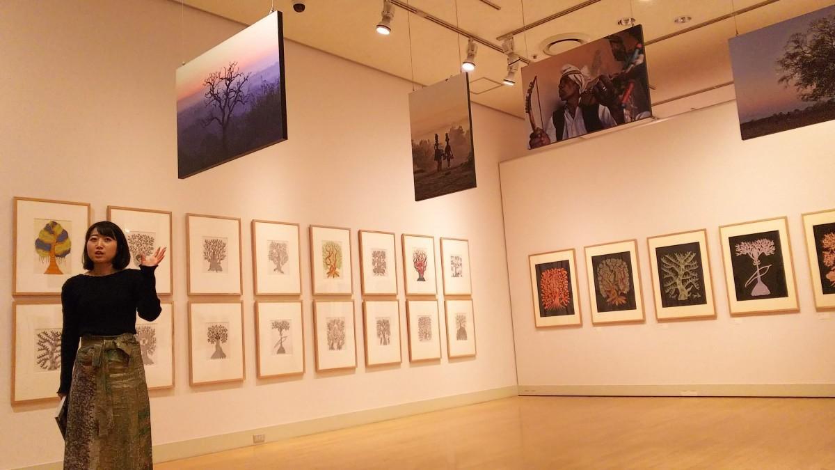「夜の木」の原画・インドの写真展示と解説する学芸員の山下さん
