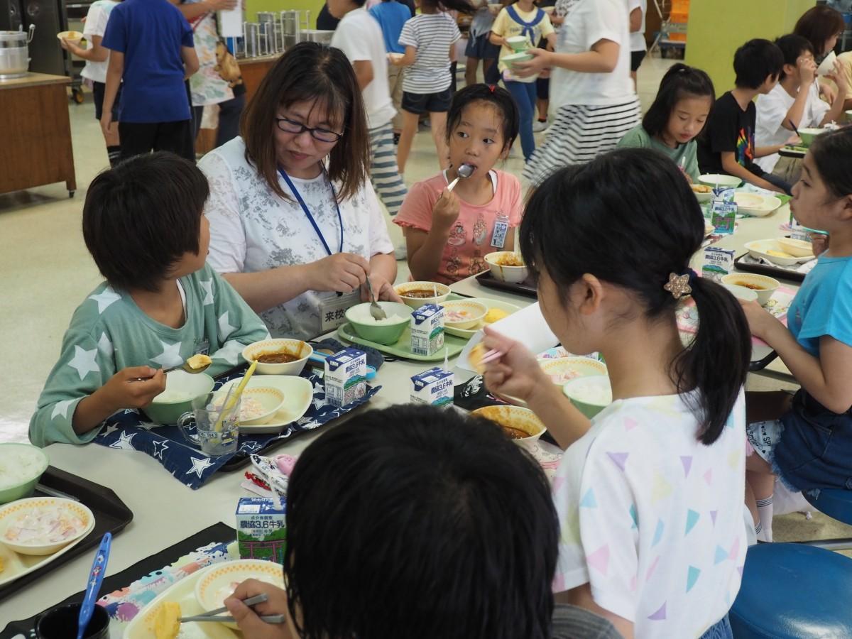 食材の生産者と一緒に給食を食べる児童
