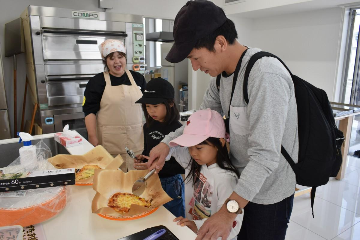 手作りピザ体験の様子。焼き上がったピザを切る参加者は自然と笑顔に