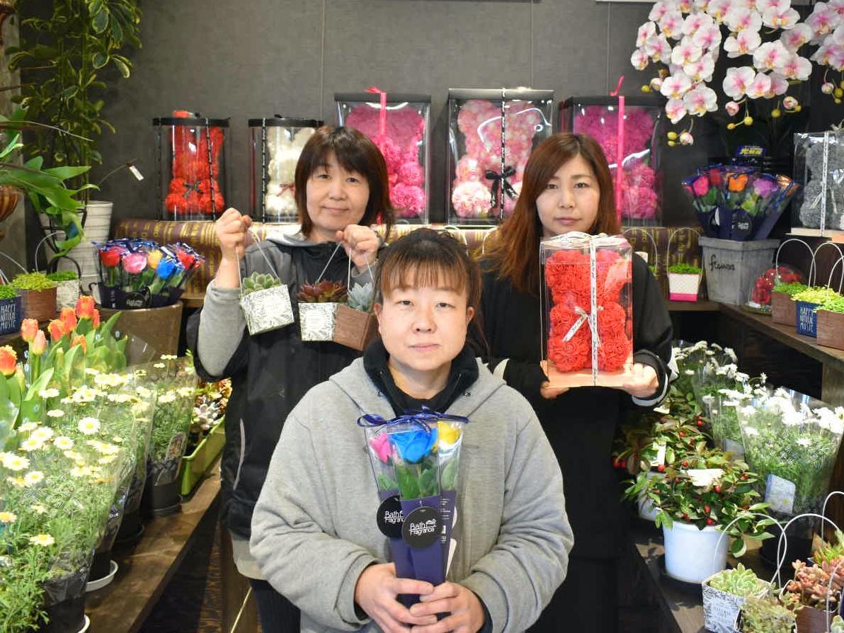 店主の横山さん(左)と従業員の2人。それぞれお薦めの品を手に