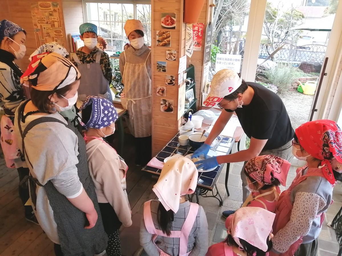 平谷さんによるピザの調理工程の説明を真剣に聞く参加者たち