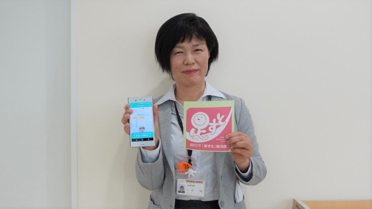 協力店の目印のシールとスマホを手にする健康増進課の小林靖さん