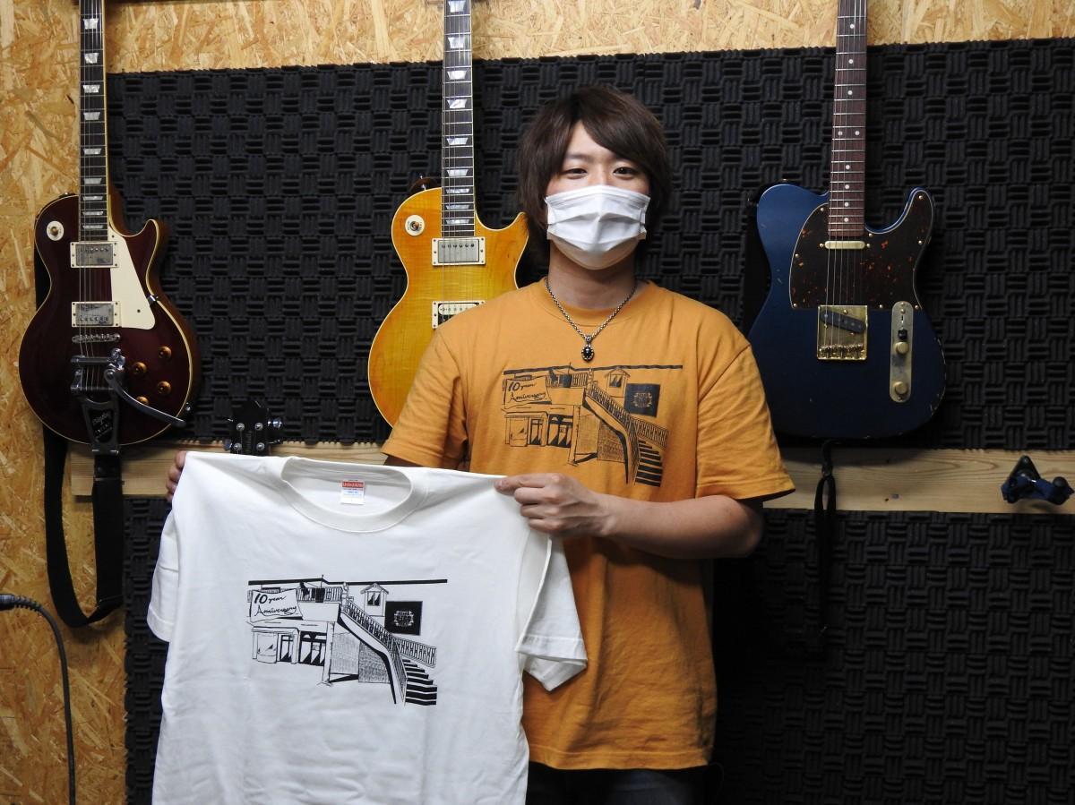 「SOUNDHOUSE PICO」の10周年記念Tシャツを持つ石原さん