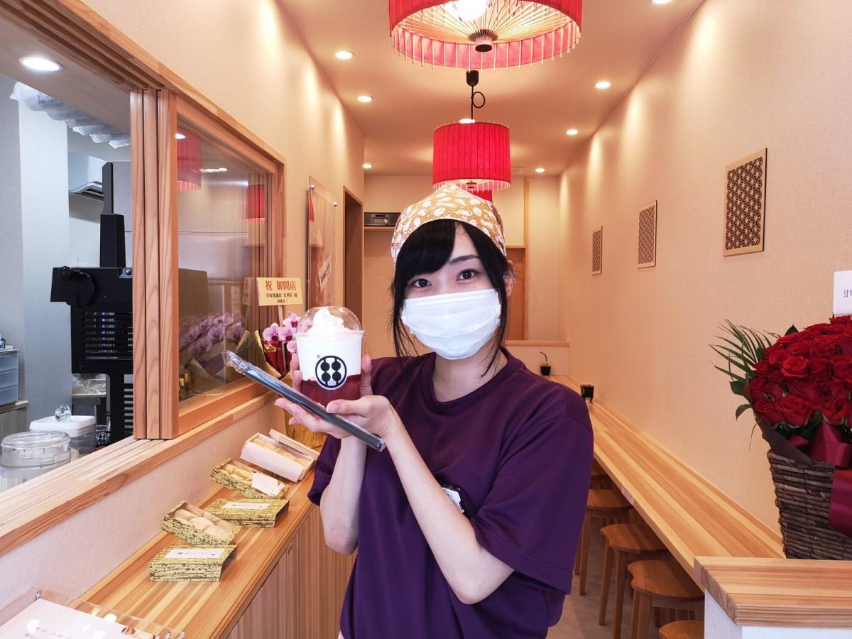 わらび餅ドリンク「贅沢いちごミルク」(690円)を持つ「甘味処 鎌倉」のスタッフ