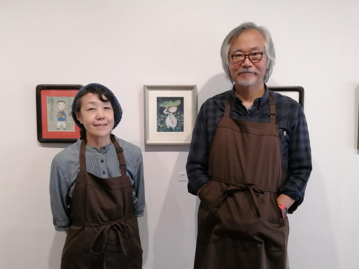 「artspace&cafe」の岩本さん夫婦。現在開催中の韓国民画展「虎と神仙」の作品の前で
