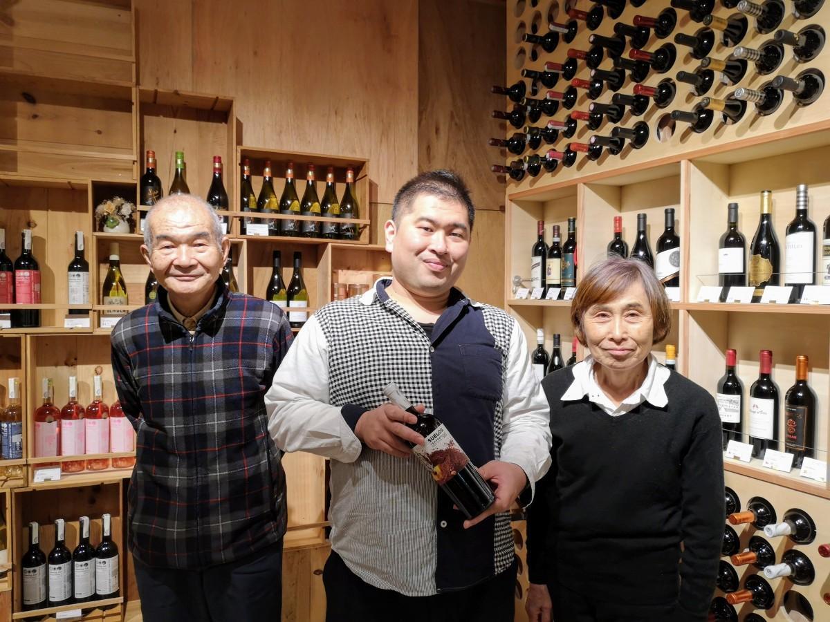 「ワインショップ和泉屋」8代目店主の泉賢一さん(中)と7代目・荘一郎さん(左)、妻の雅子さん(右)