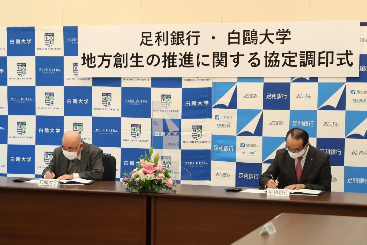 奥島孝康白鴎大学学長(左)と清水和幸足利銀行頭取(右)