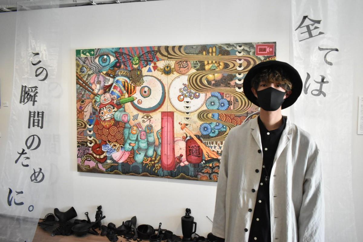飯山太陽さん。1年がかりで描き上げた作品「全てはこの瞬間のために。」の前で。
