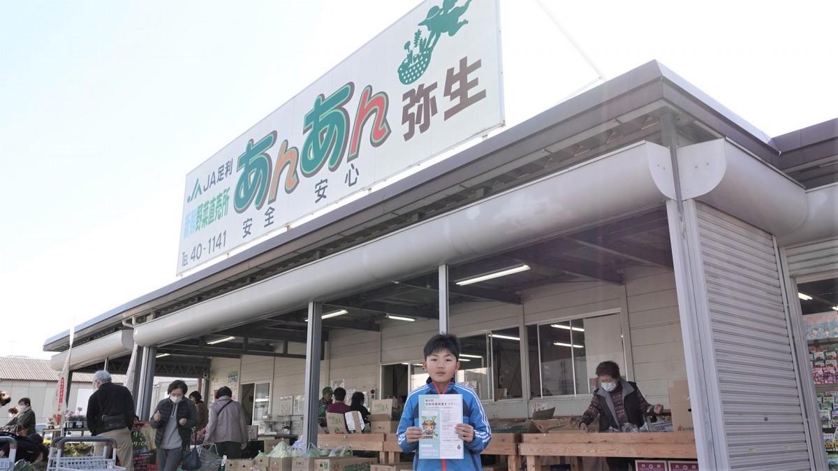 参加店の「JA足利あんあん弥生」前でスタンプカードを持つ来場客の山地さん