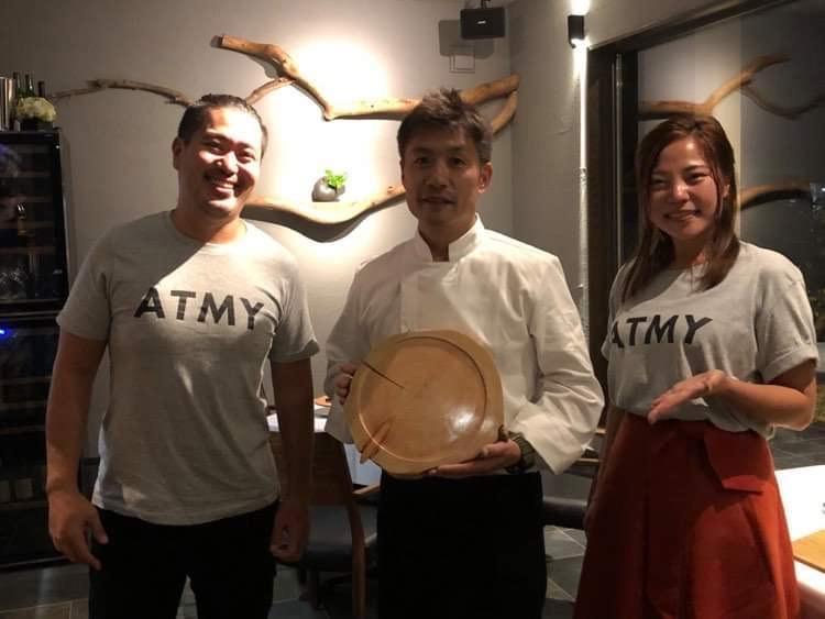 完成した間伐材プレートを掲げる三浦シェフと熱海キコリーズのメンバー