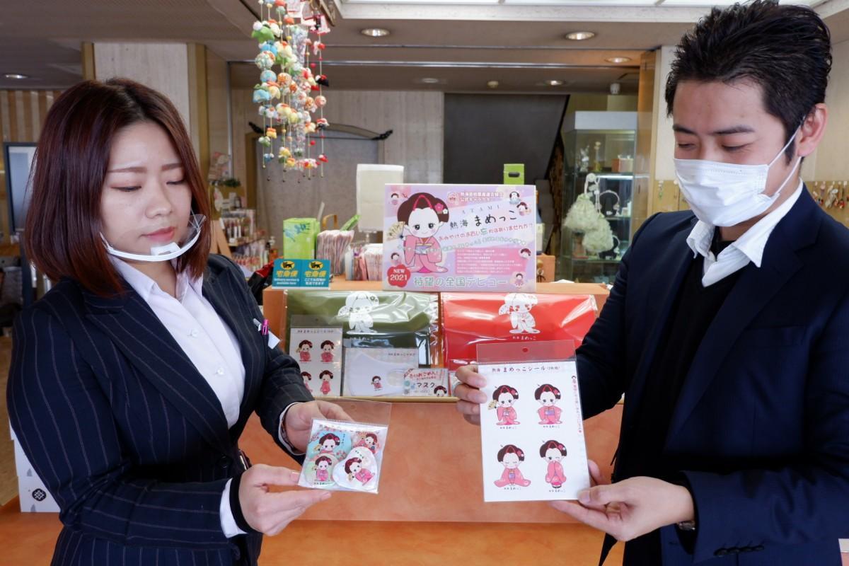 「まめっこ」グッズを掲げる谷清和さんと宮城祐子さん