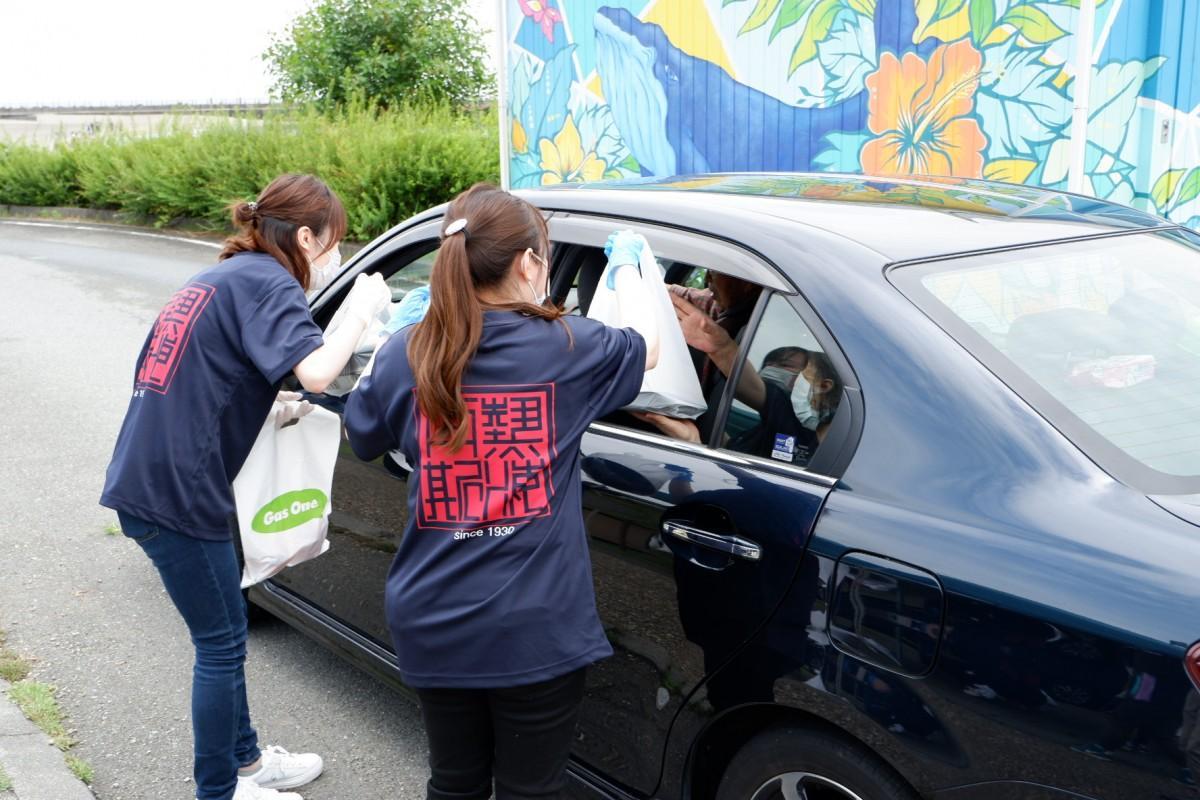 「ドライブスルー」で乗車したまま弁当を受け取る参加者
