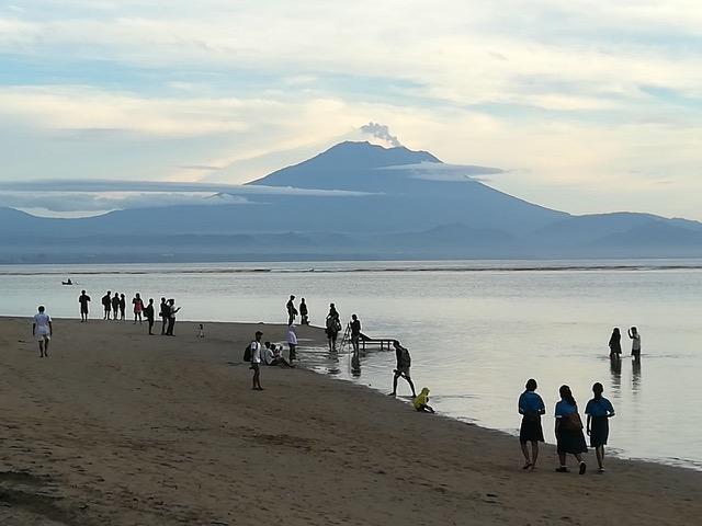 アグン山をバックにビーチクリーニングの参加者ら