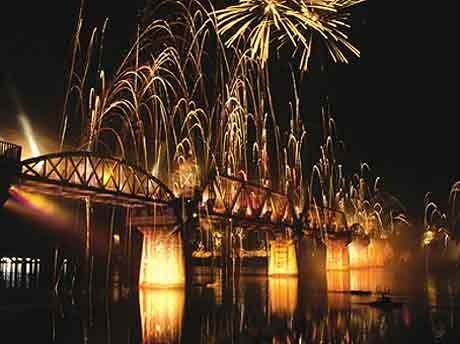 ライトアップされた鉄橋の上に打ち上げられる花火。