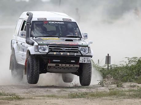 土煙を上げコースを駆け抜けるレースカー(アジアクロスカントリーラリー日本事務局提供)