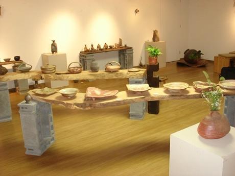 写真=信楽焼の新鋭作家・水垣力さんの個展の様子。茶器、酒器などの陶器102点が並ぶ。
