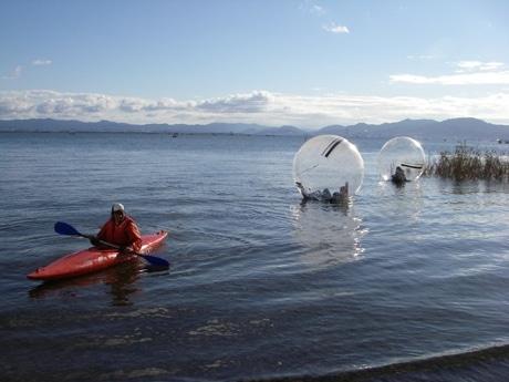 写真=ウォーターボールをカヌーで引っ張って、ゆっくり水面を移動する様子。