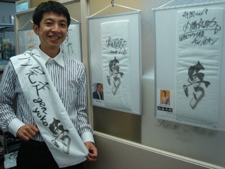 写真=前回の叶えた夢「夫婦でホノルルマラソン完走」の「夢タオル」を持つ寺田社長。