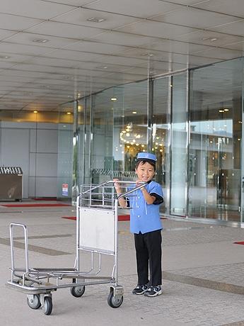 大津プリンスホテルの前でポーズをとるベルボーイに扮した男の子。