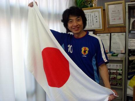日本代表のユニホームを着用し「日の丸タオル」で応援する寺田社長。