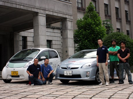 次世代自動車「プリウスプラグインハイブリッド」と電気自動車「i-MiEV」を前にする「ZEVEX」のメンバー。