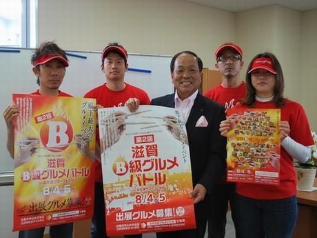 出店グルメ記者発表の後、ポスターを手にする大道会長と実行委員会メンバー