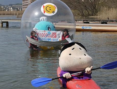 キャッフィーと一緒に「ウォーターボール」を楽しむ長田さん夫妻。おおつ光ルくんがカヌーでエスコート