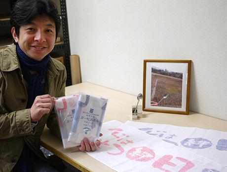 完成した「福興応援ガーゼタオル」と寺田さん。南三陸を訪れた際、津波被害の荒涼とした風景の中、足元に残されていたスプーンを目にする。そこに確かにあった生活に心を打たれたという