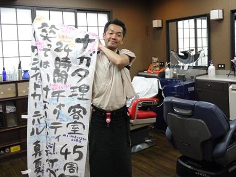 お客さんがイベントの成功を祈って寄せ書きしたのぼりを手にする店主の長田浩さん