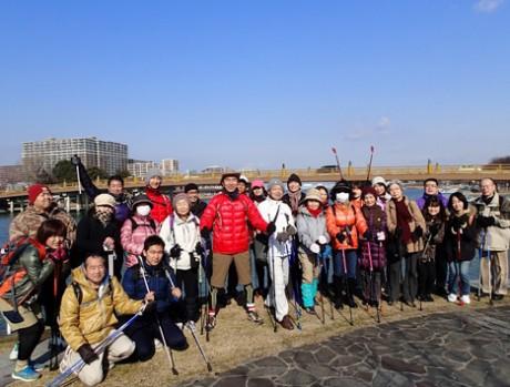 全長260メートルの瀬田の唐橋を東に渡った所で記念撮影。ツアーは、ポールを持って全身の筋肉を使って歩く「ノルディックウオーク」。川本勇さん(2列目の左から5人目)はワンダーフォーゲル部出身でもある