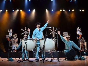 電機メーカー社員の衣装でユーモアあふれる電動楽器を演奏するアートユニット・明和電機による「メカニカルライブ」