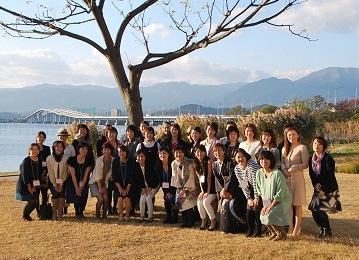 琵琶湖大橋とススキを背景に開催地ホテル「セトレ マリーナびわ湖」の庭で記念撮影。太陽の光を浴びて輝く女性社長たち