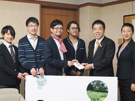 三日月大造県知事に寄付を手渡すミナクサPG(プロジェクトクトグループ)のメンバー