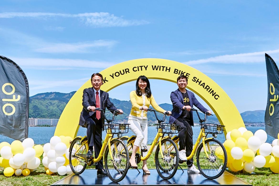 琵琶湖岸で自転車に乗るまちづくり大津山本代表、越大津市長、OFO JAPANの日吉代表