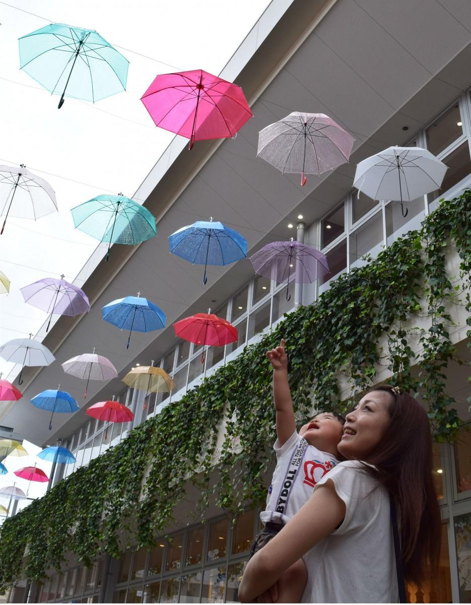 傘に手を伸ばす岩崎瑠莉ちゃん1歳