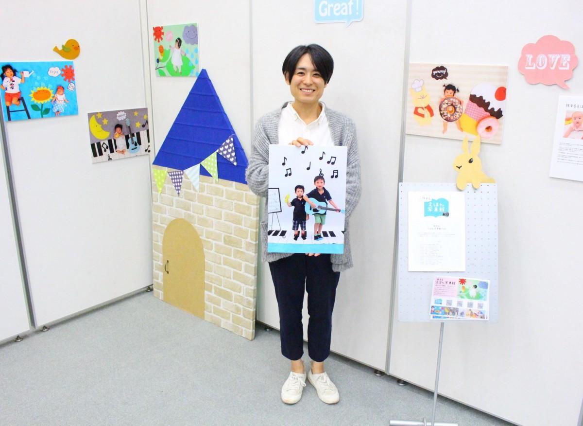 展示会場でパネルを持つ伊藤朋子さん