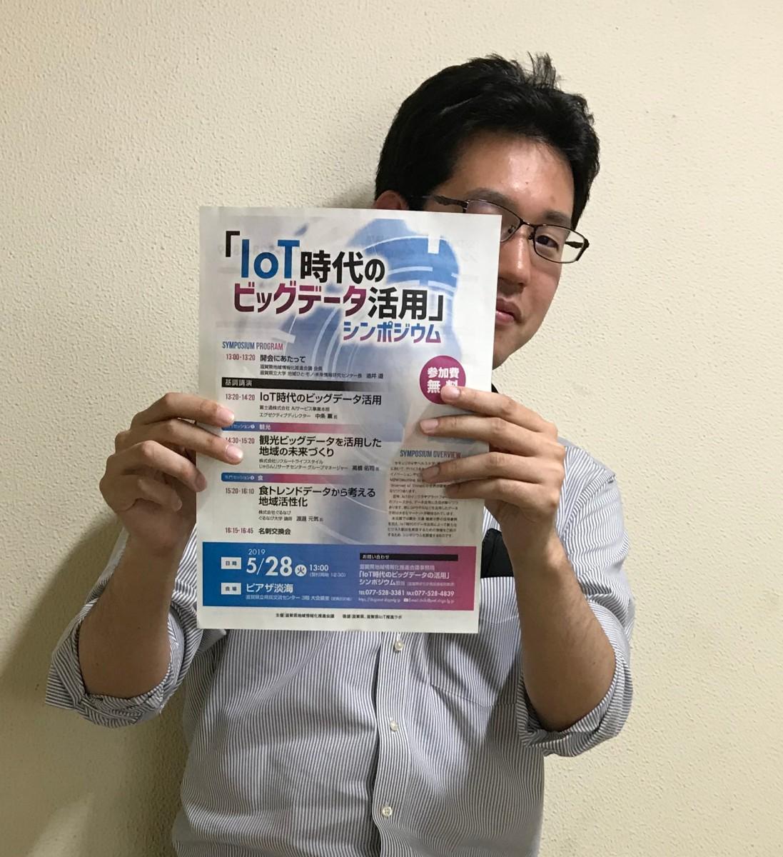 シンポジウムのチラシを持つ「滋賀県地域情報化推進会議」の担当者
