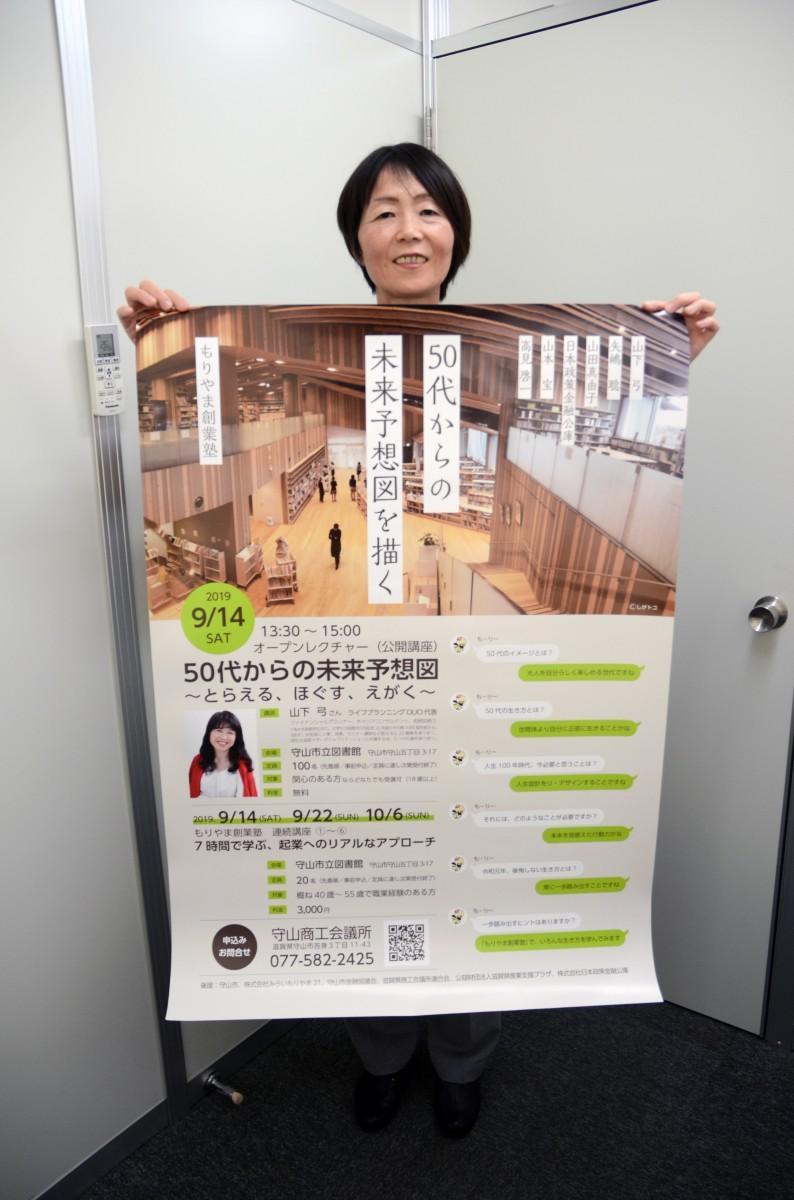 ポスターを持つ岡田さん