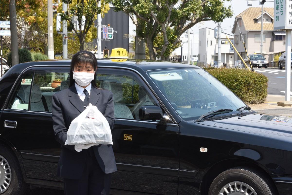 テークアウトした料理を届ける守山タクシーの運転手