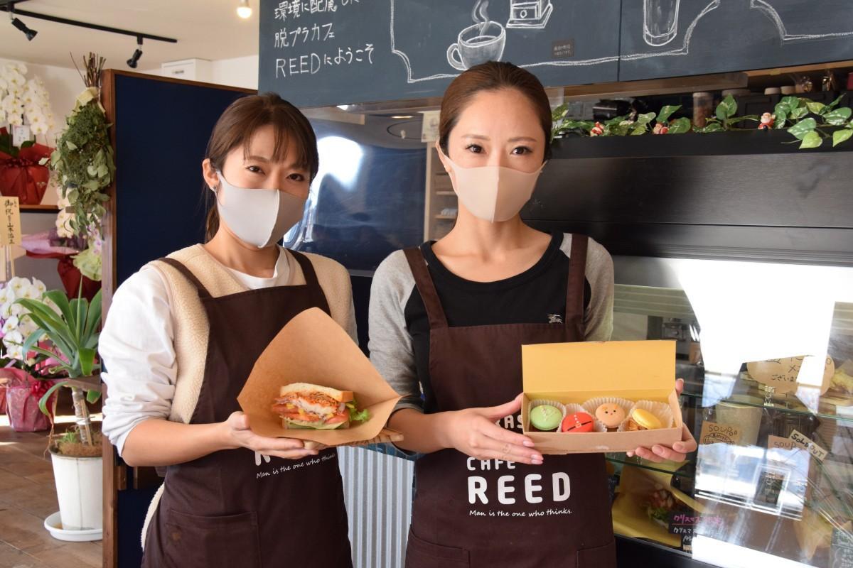 「トゥンカロン」とサンドイッチを持つ「CAFE REED」のスタッフ