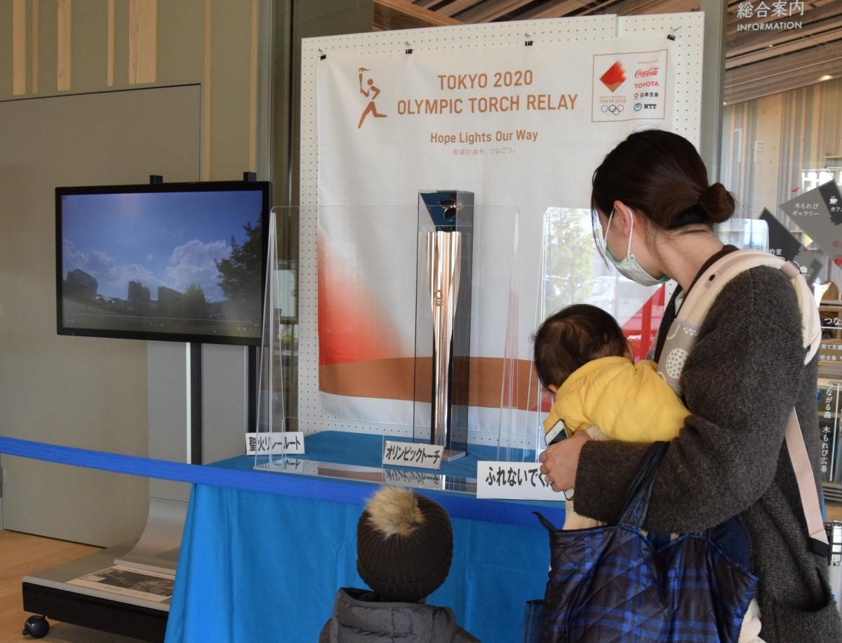 守山市立図書館でオリンピックの聖火リレートーチを見る親子