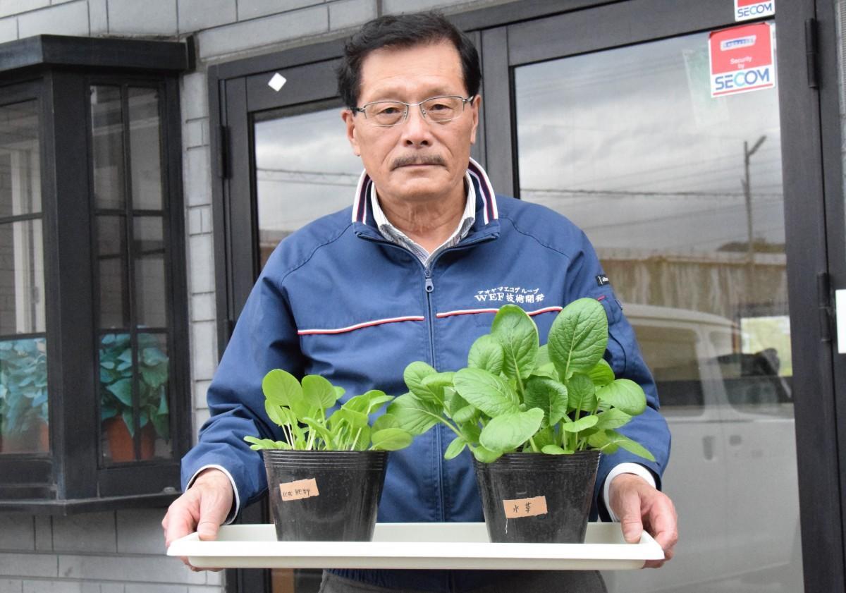 水草堆肥で育て、大きく育った野菜を持つWEF技術開発の青山章さん