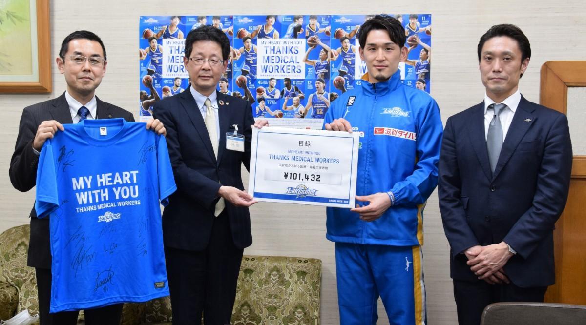滋賀レイクスターズは、滋賀県に寄付金と選手のサイン入りTシャツを寄贈した