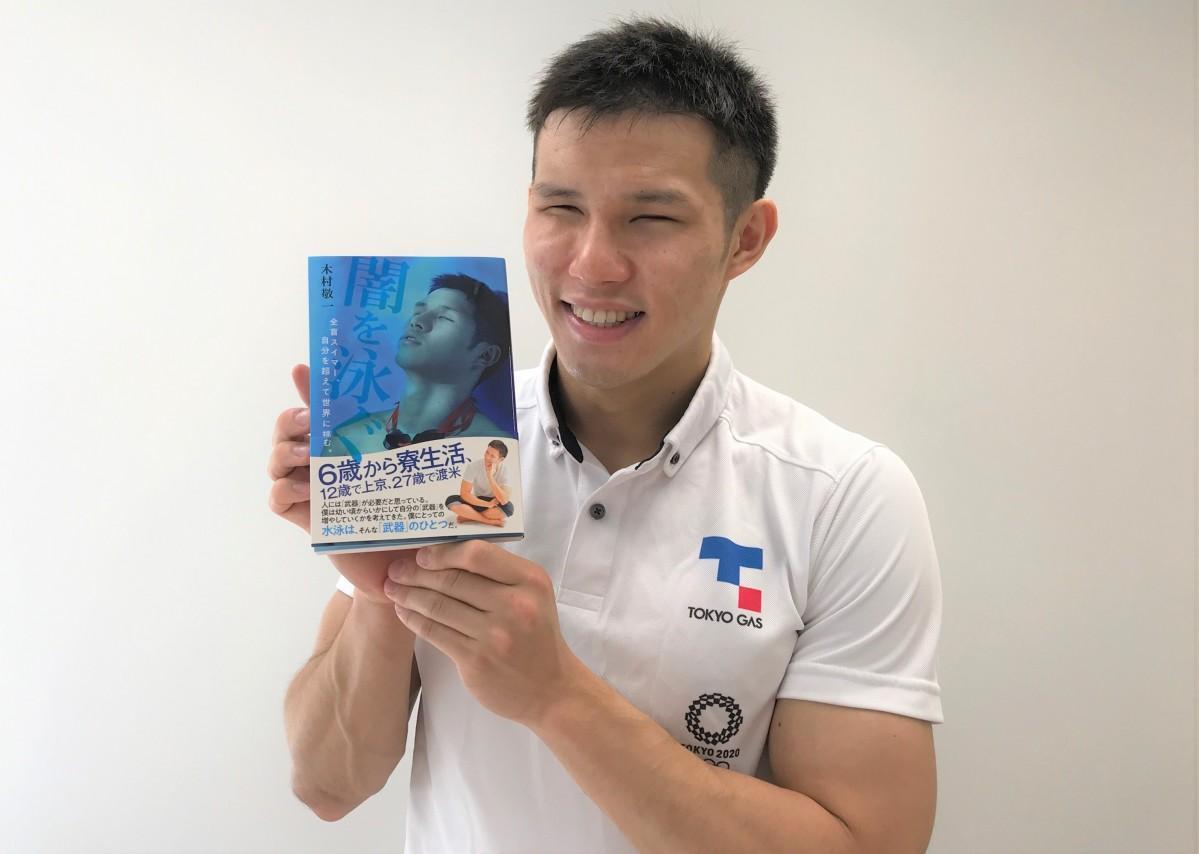 自伝「闇を泳ぐ」を手に持つ木村敬一選手(写真提供:東京ガス)